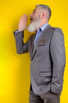 Reifer bärtiger mann des studioporträts im grauen geschäftsanzug schreit und ruft beiseite, such- und anrufkonzept, gelber hintergrund.
