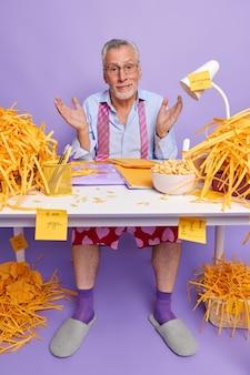 Reifer bärtiger mann weiß nicht, wie man einen finanzbericht erstellt sieht mit ahnungslosem ausdruck aus arbeit im home office trägt hauskleidung hat viel zu tun kann sich nicht entscheiden, womit ich anfangen soll.