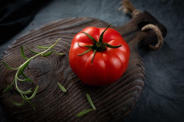 Reifer bio-tomaten-rosmarin-zweig auf einem alten schneidebrett