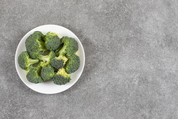 Reifer brokkoli auf einem teller auf dem marmortisch.