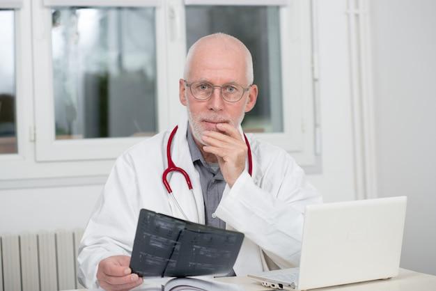 Reifer doktor, der röntgenstrahl, in seinem büro überprüft