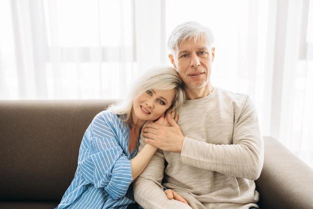 Reifer ehemann und ehefrau sitzen auf couch und umarmungen, glückliche familie. erwachsenes liebespaar, das zu hause ruht