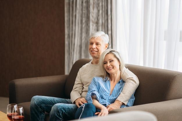 Reifer ehemann und ehefrau sitzen auf couch und umarmungen