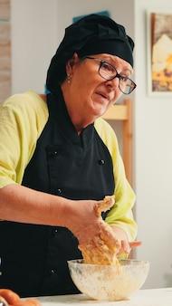 Reifer erfahrener bäcker, der ein kulinarisches rezept-tutorial mit moderner kamera in der küche mit knochen und schürze aufzeichnet. influencer-koch, der internet-technologie verwendet, um in sozialen medien zu kommunizieren.