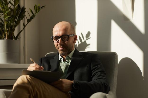 Reifer ernsthafter geschäftsmann in brillen, die auf sessel sitzen und notizen im dokument machen, das er im büro arbeitet