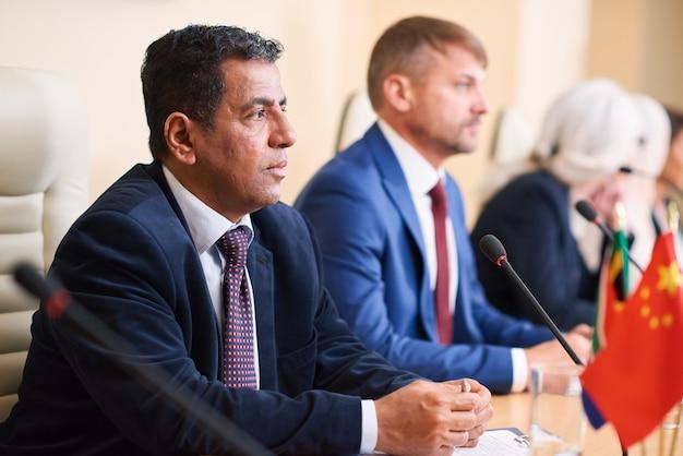 Reifer ernsthafter politiker, der einem kollegen auf einer konferenz mit anderen delegierten zuhört
