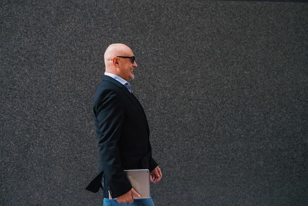 Reifer ernsthafter professioneller eleganter glücklicher geschäftsmann in einem anzug hält eine tablette beim gehen