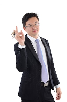 Reifer erwachsener asiatischer chinesischer geschäftsmann, der einen neuen schlüssel über weißem hintergrund hält