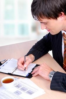Reifer erwachsener mann, der vom tisch sitzt und auf persönliches datumsbuch schreibt