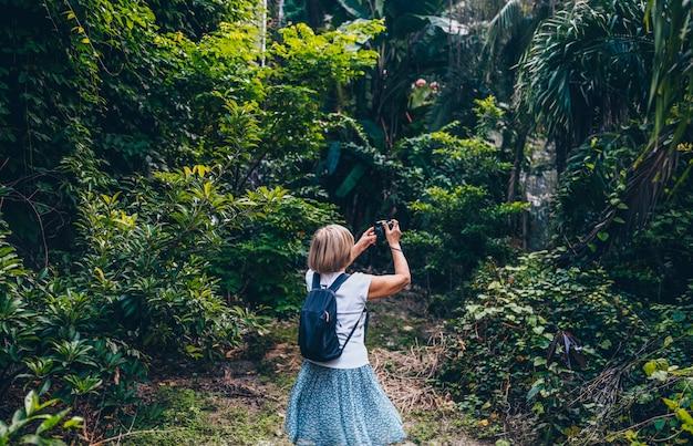 Reifer frauentourist des älteren älteren asiatischen reisenden wanderers, der das machen von fotos in sanya-dschungel genießend geht. entlang asien reisen, aktives lebensstilkonzept. entdecken sie hainan, china