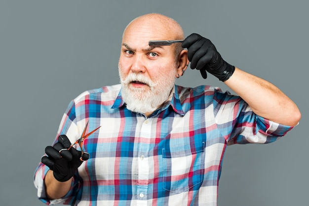 Reifer friseur mit schere und rasiermesser. vintage friseursalon, rasieren.