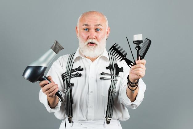 Reifer friseurfriseur im friseursalon. alter aufgeregter überraschter friseur mit friseurausrüstungswerkzeugen