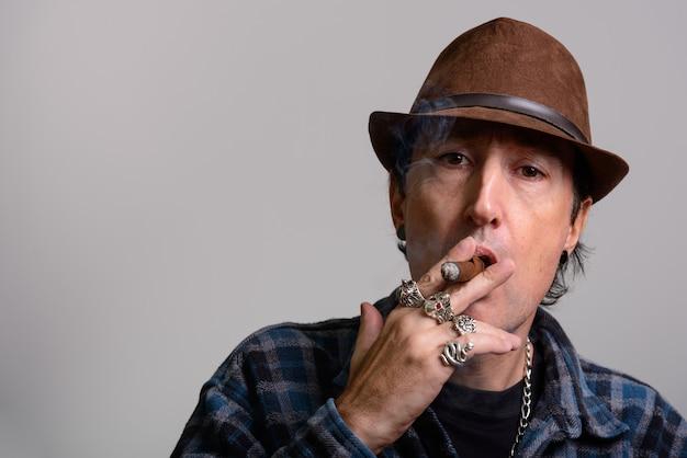 Reifer gangstermann, der beim rauchen der zigarre hält