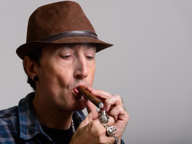 Reifer gangstermann, der zigarre anzündet