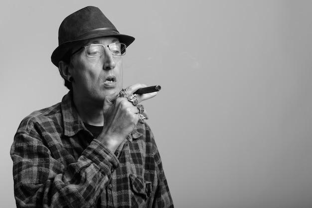 Reifer gangstermann, der zigarre in schwarzweiss raucht
