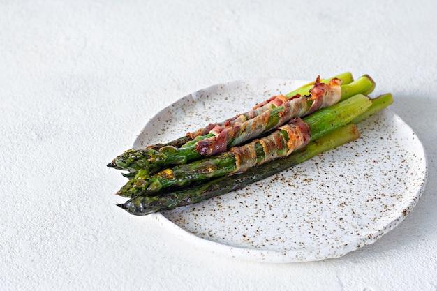 Reifer gebackener spargel mit speck, beilage zum frühstück, mittagessen, grillen.