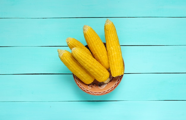 Reifer gekochter mais auf blauem holztisch, draufsicht
