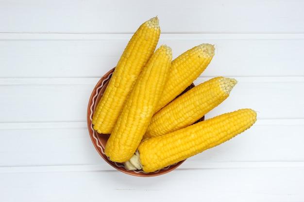 Reifer gekochter mais auf weißem holztisch, draufsicht