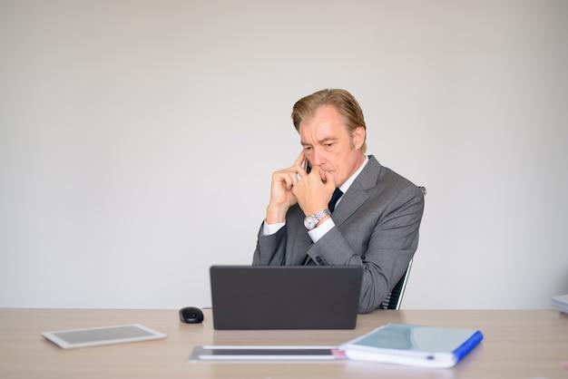 Reifer geschäftsmann, der beim telefonieren bei der arbeit denkt