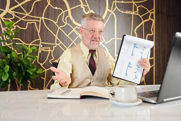 Reifer geschäftsmann, der diagramm mit finanzbericht zeigt, wenn video-geschäftspartner anruft