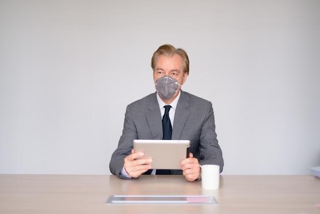 Reifer geschäftsmann, der digitales tablett mit maske zum schutz vor ausbruch des koronavirus bei der arbeit verwendet
