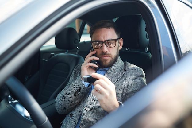 Reifer geschäftsmann, der im autosalon sitzt und auf handy spricht