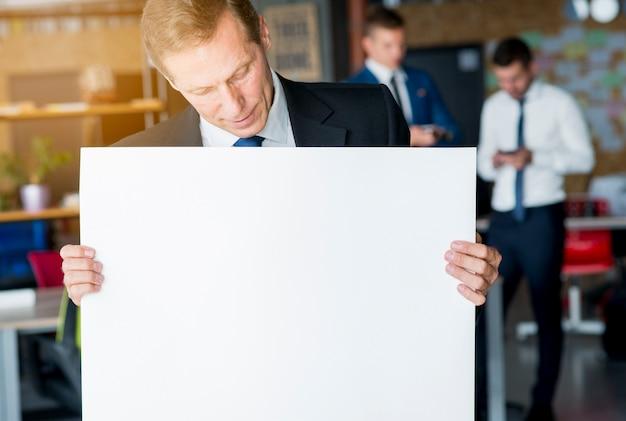 Reifer geschäftsmann, der leeres weißes plakat betrachtet