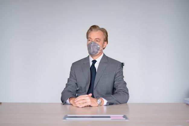 Reifer geschäftsmann, der mit maske zum schutz vor ausbruch des koronavirus bei der arbeit arbeitet