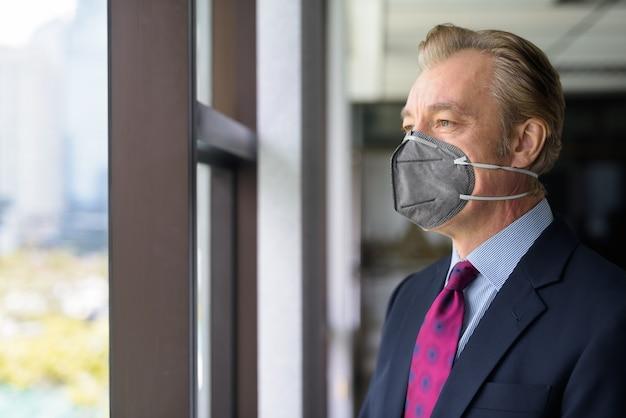 Reifer geschäftsmann, der mit maske zum schutz vor dem ausbruch des koronavirus aus dem fenster denkt und schaut