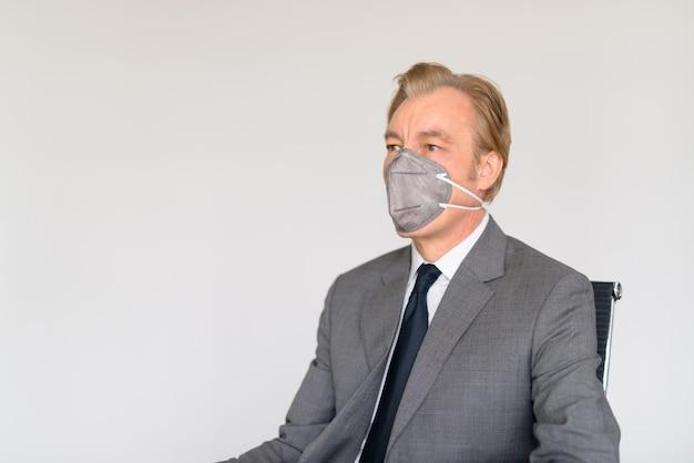 Reifer geschäftsmann, der mit maske zum schutz vor dem ausbruch des koronavirus bei der arbeit denkt