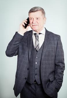 Reifer geschäftsmann, der mit smartphone telefoniert