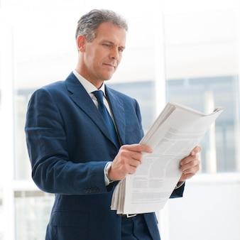 Reifer geschäftsmann, der nachrichten im büro liest