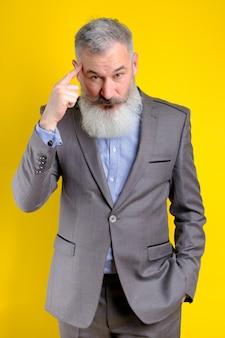 Reifer geschäftsmann des studio-porträts gekleidet in grauem anzug, der mit zeigefinger auf kopf zeigt, großartige idee oder gedankenkonzept, gutes gedächtnis, gelber hintergrund.
