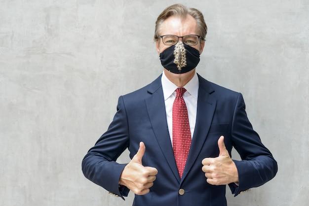 Reifer geschäftsmann im anzug, der maske trägt und daumen gegen betonwand gibt