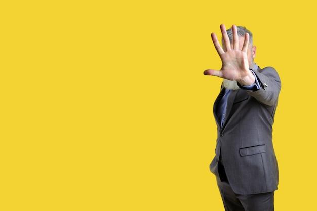 Reifer geschäftsmann im grauen anzug zeigt handstoppschild, geste nicht mehr, gelber hintergrund, kopienraum