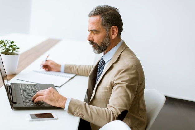 Reifer geschäftsmann in der klassischen klage unter verwendung eines laptops beim arbeiten in seinem büro