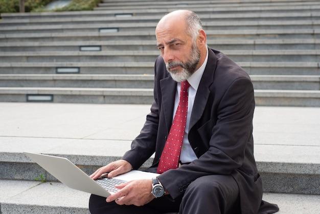 Reifer geschäftsmann mit laptop-computer auf straße