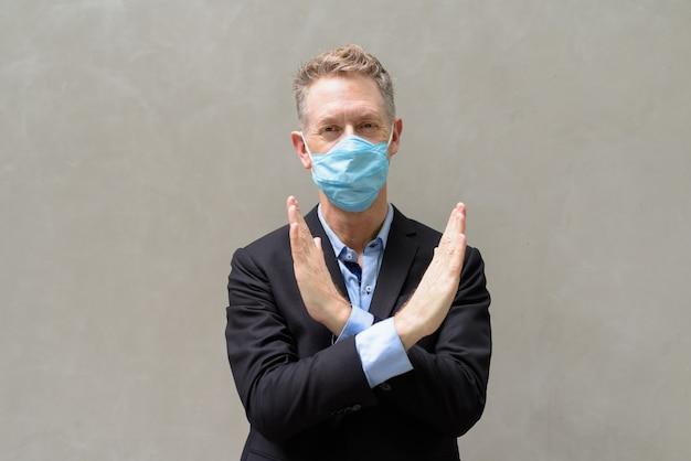 Reifer geschäftsmann mit maske, die stoppgeste im freien zeigt