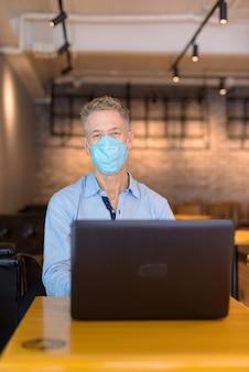 Reifer geschäftsmann mit maske unter verwendung des laptops beim sitzen am kaffeehaus