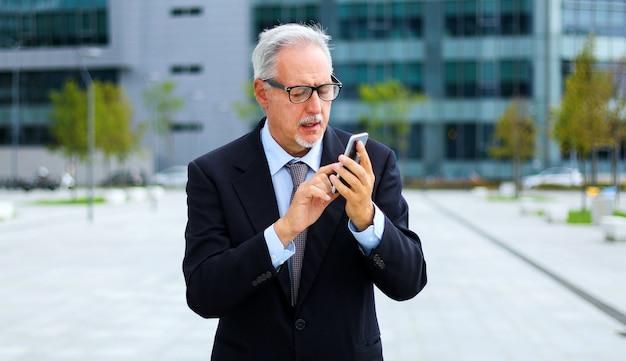 Reifer geschäftsmann mit smartphonestellung