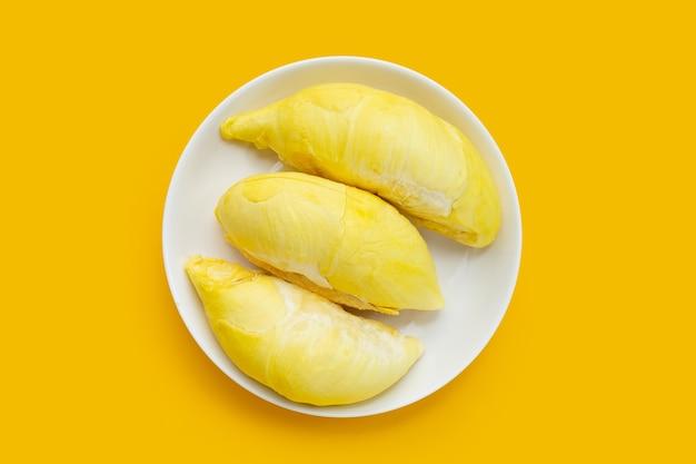 Reifer geschnittener durian in weißer platte auf gelbem hintergrund.