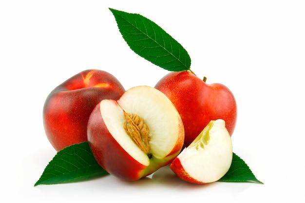 Reifer geschnittener pfirsich (nektarine) mit den grünen blättern lokalisiert auf weißem hintergrund
