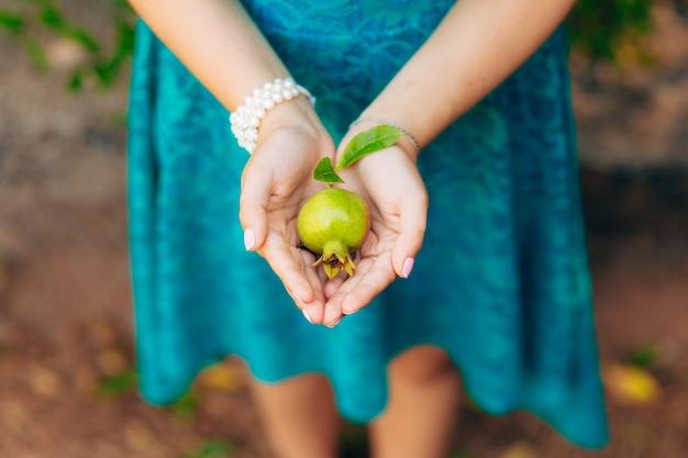 Reifer granatapfel in händen auf der natur