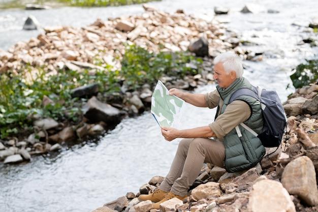Reifer grauhaariger rucksacktourist, der die karte seines zielortes liest, während er sich am fluss ausruht