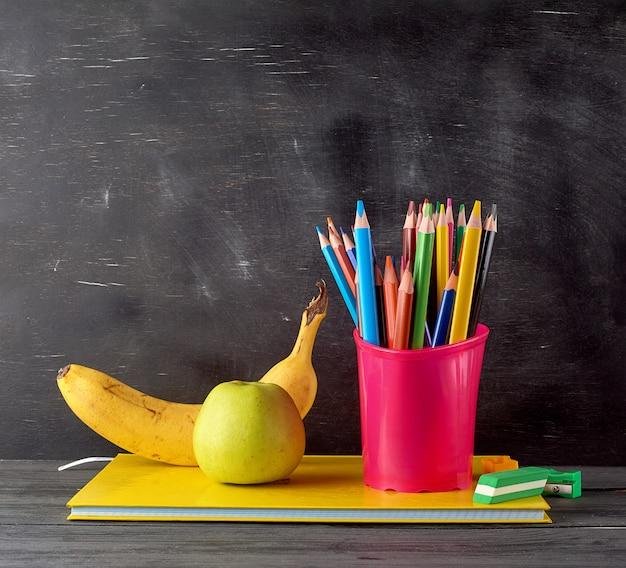 Reifer grüner apfel, banane auf einem stapel notizbüchern