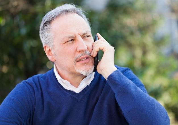 Reifer gutaussehender mann, der am telefon in einem park spricht