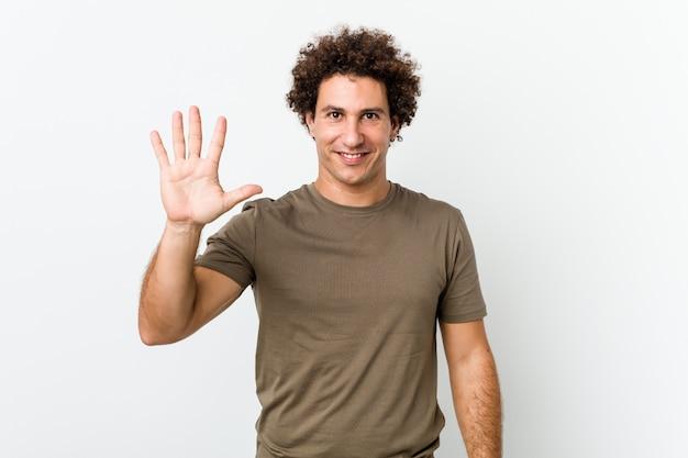 Reifer gutaussehender mann lokalisierte lächelnde nette darstellende nr. fünf mit den fingern.