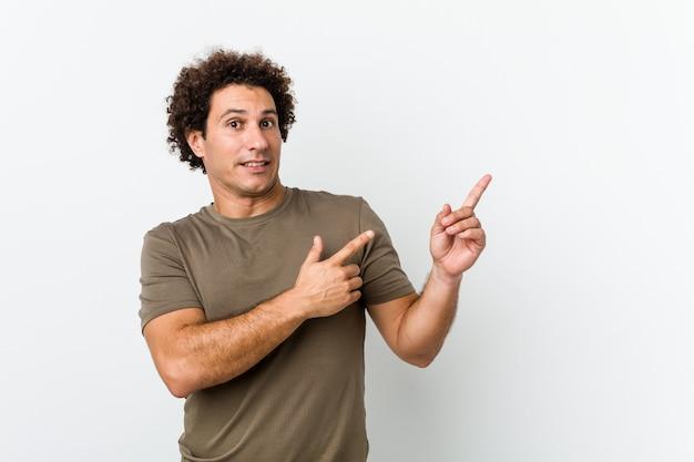 Reifer gutaussehender mann lokalisiertes entsetztes zeigen mit den zeigefingern auf einen kopienraum.