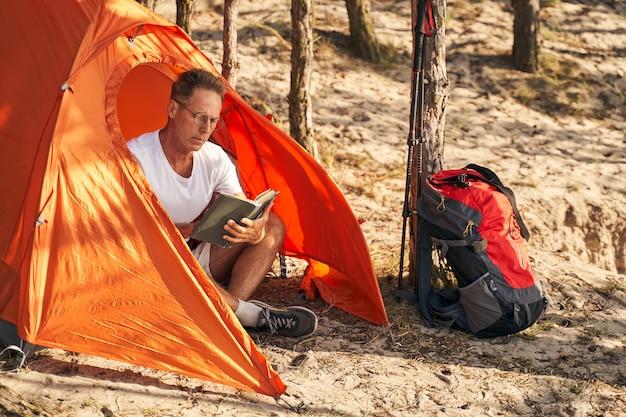 Reifer gutaussehender mann mit brille ruht sich nach nordic walking im wald aus und liest literatur