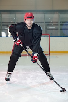 Reifer hockeyspieler in schutzhelm und handschuhen, der sich vor der kamera die eisbahn hinunter bewegt und dich ansieht, während er puck schießen wird